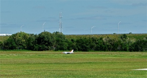 Radio-controlled plane taking off at airfield