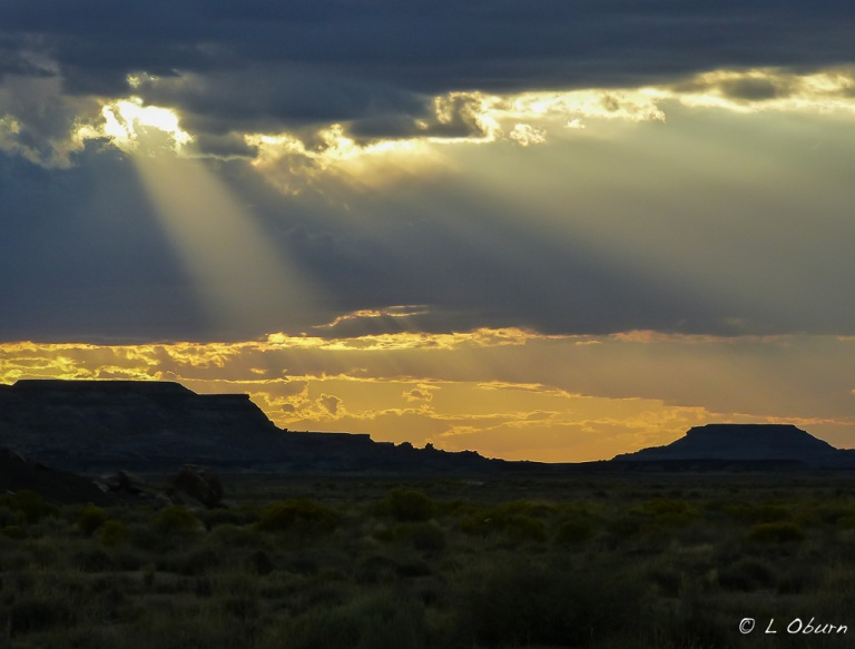 The sun peering through clouds over the Petrified Forest