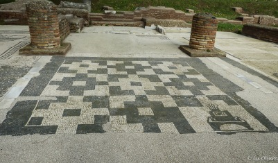 This chessboard-like mosaic has a lighthouse symbol in the lower right-hand corner, the symbol of the port of Ostia.