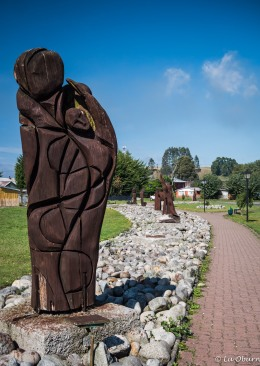 Sidewalk lined with wooden sculptures.